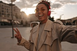 Attractive brunette woman in red headphones smiling and taking selfie outside. Dark-skinned lady shows peace sign.