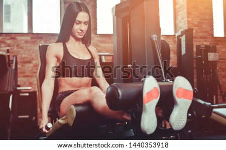 Attractive brunette woman in sportswear doing leg extension exercise in an exercise machine at the gym