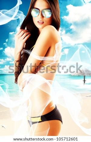 attractive brunette woman in white fabric on the beach