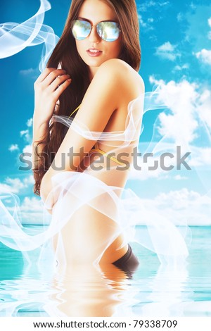 attractive brunette woman in white fabric on the beach in water