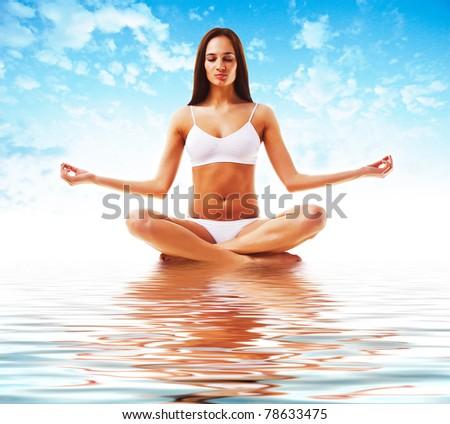 attractive brunette woman in yoga poseattractive brunette woman in yoga pose and sky