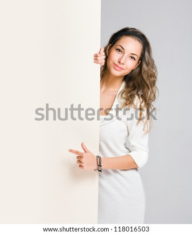 Attractive brunette woman pointing at large blank white banner.