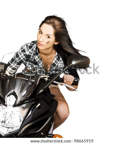 Attractive brunette woman riding a large motorbike during a race while leaning in to a corner with flying long hair