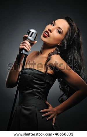 Attractive brunette woman with a retro microphone