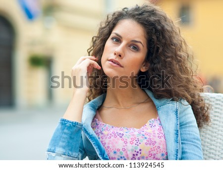 attractive brunette woman with long curly hair portrait sitting in outside cafe
