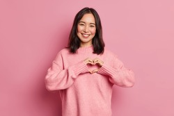 Attractive brunette young Asian woman feels happy and romantic shapes heart gesture expresses tender feelings wears casual jumper poses against pink background. People affection and care concept
