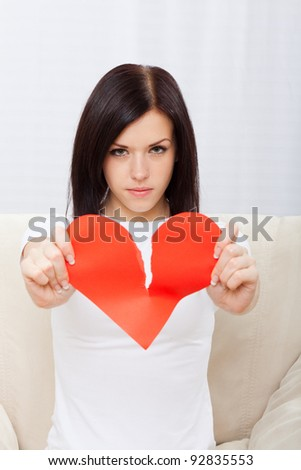 Attractive brunette young girl holding broken paper red valentine heart, woman sitting on couch at home, concept of unhappy love valentine's day