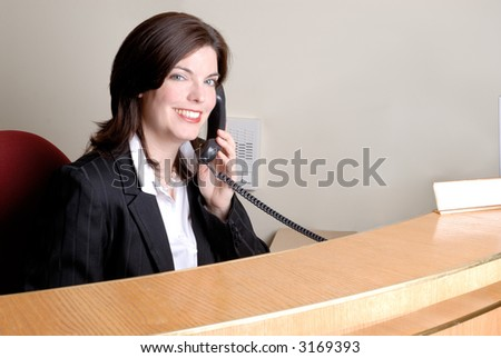 Attractive Brunette Young Woman Answering The Phone At A Company Reception Desk