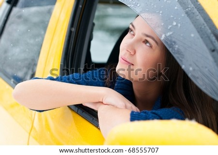 Attractive brunette young woman in a yellow car