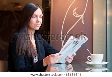 Attractive brunette young woman reads a magazine sitting in a cafe, shallow DOF, focus on face