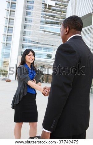 Attractive business man and women team at office building shaking hands - stock photo