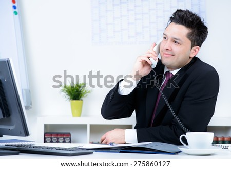 attractive business man in office speaking at telephone