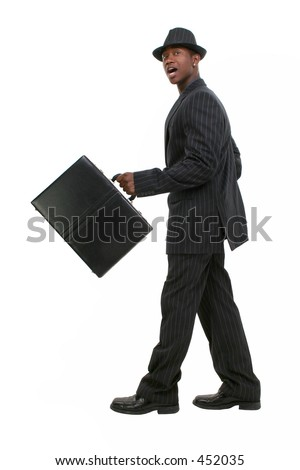 Attractive Business Man In Pin Striped Suit & Hat. Full body shot walking with briefcase.