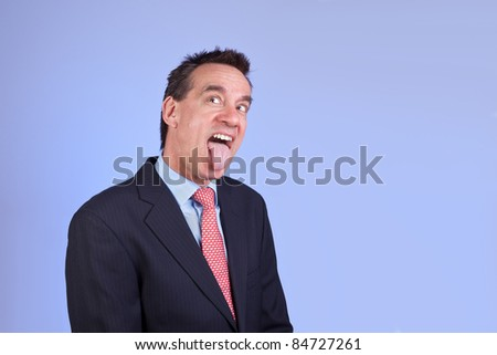 Attractive Business Man in Suit Sticking out Tongue on Blue Background