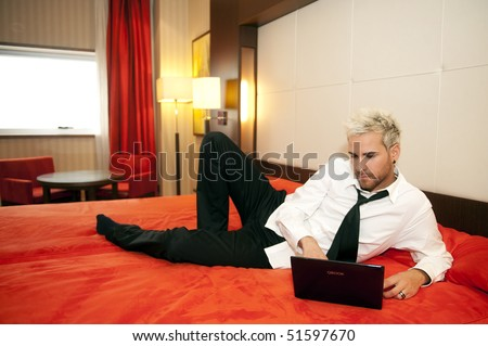 Attractive business man on his laptop in bed