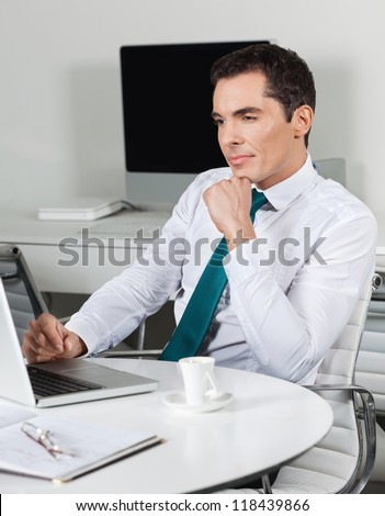 Attractive business manager working with laptop at office desk