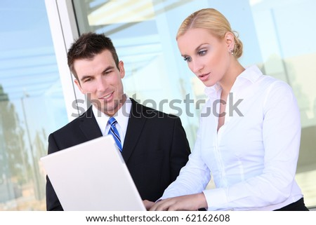 Attractive business team on laptop at office (Focus on Man)