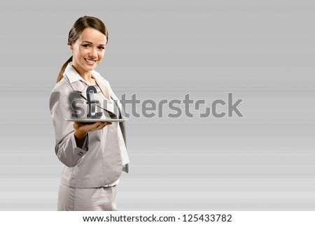 attractive business woman holding a tablet with british pound, place for text