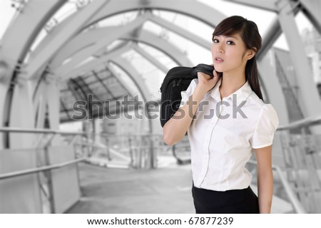 Attractive business woman of Asian holding briefcase inside of modern architecture of flyover.