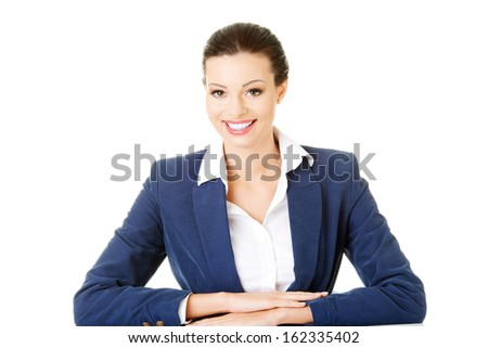 Attractive business woman sitting and smiling.  Isolated on white.