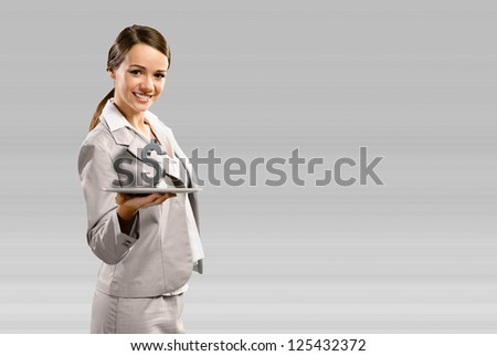 attractive business woman smiling and holding a tablet, with a dollar sign, concept of business success