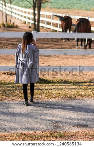 Attractive Business woman talking on mobile phone while visiting her farm. A combination of business dressing with a rural landscape. The owner visits his horses in the countryside. #1240565134