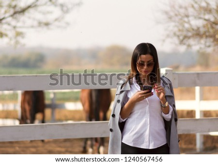 Attractive Business woman talking on mobile phone while visiting her farm. A combination of business dressing with a rural landscape. The owner visits his horses in the countryside. #1240567456