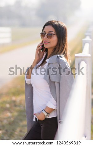 Attractive Business woman talking on mobile phone while visiting her farm. A combination of business dressing with a rural landscape. The owner visits his horses in the countryside. #1240569319