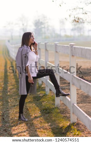 Attractive Business woman talking on mobile phone while visiting her farm. A combination of business dressing with a rural landscape. The owner visits his horses in the countryside. #1240574551