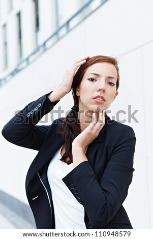 Attractive business woman touching her face with her hands
