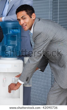 Attractive businessman filling cup from water cooler in the office