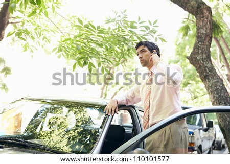 Attractive businessman leaning on a car's top while making a phone call in a leafy street.