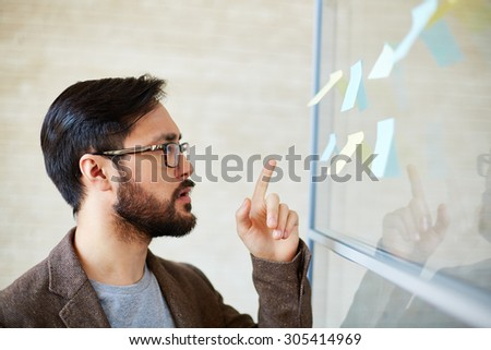 Attractive businessman pointing at notepaper on board #305414969