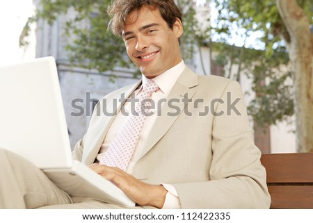Attractive businessman sitting on a wooden bench in a classic city using a laptop computer, smiling.