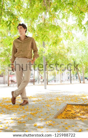 Attractive businessman standing in a city park under green trees in blossom, holding his smart phone in his hand, smiling.