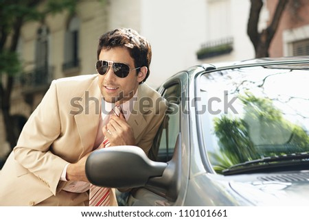 Attractive businessman tightening his tie while looking at himself in a car's reversing mirror, smiling.