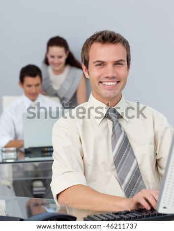 Attractive businessman working at his computer in the office