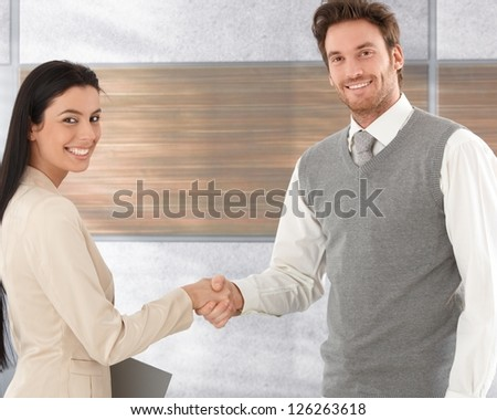 Attractive businesspeople shaking hands, smiling happily.