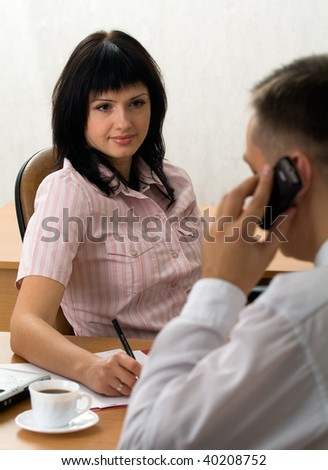 Attractive businesswoman and a guy making a call
