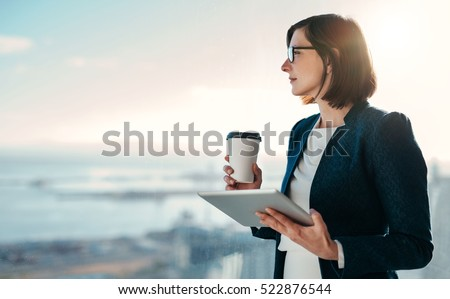 Attractive businesswoman drinking a coffee and using a digital tablet while standing at a window in an office overlooking the city stock photo