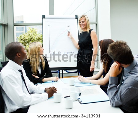 Attractive businesswoman giving a presentation to her team