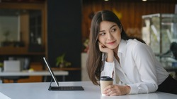 Attractive businesswoman holding cup of hot drink and looking away with smile while sitting in office.