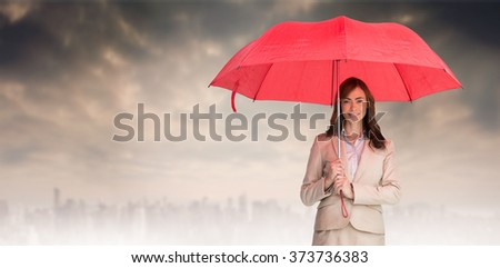 Attractive businesswoman holding red umbrella against dusty path leading to large city