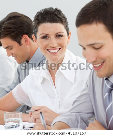 Attractive businesswoman in a meeting with her team looking at the camera