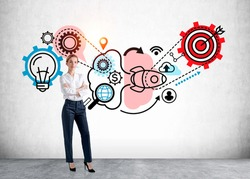 Attractive businesswoman in crossed arms pose, standing near drawing with gears, target and light bulb. Icons drawn on concrete wall. Task and goal, concept of human intelligence and plan