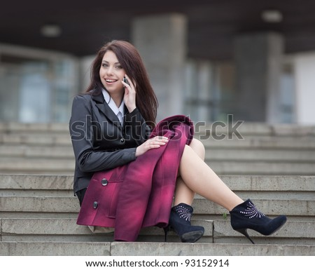 Attractive businesswoman on open air. Girl sitting on stairs talking on the phone