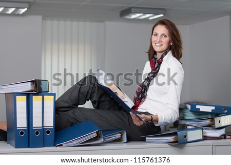 Attractive businesswoman sits on a desk surrounded by stacks of files