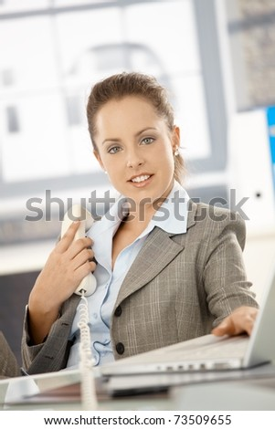 Attractive businesswoman sitting at desk in office, holding phone, having laptop, smiling.