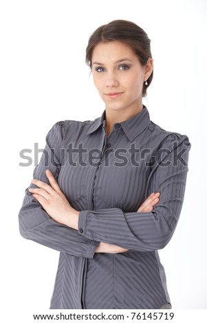 Attractive businesswoman standing arms crossed, looking at camera.?