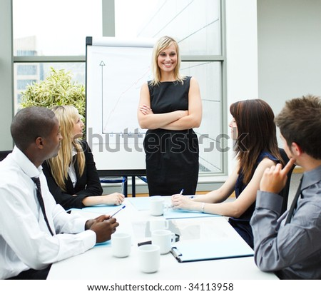 Attractive businesswoman standing in a meeting with folded arms